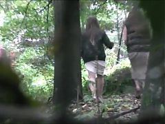 Voyeur is spying and recording two girl pissing in the wood